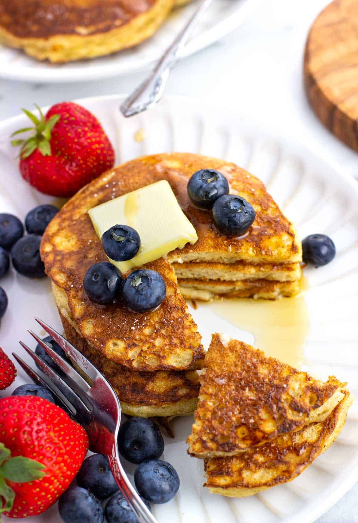 A stack of pancakes topped with a pat of butter with a wedge cut out.