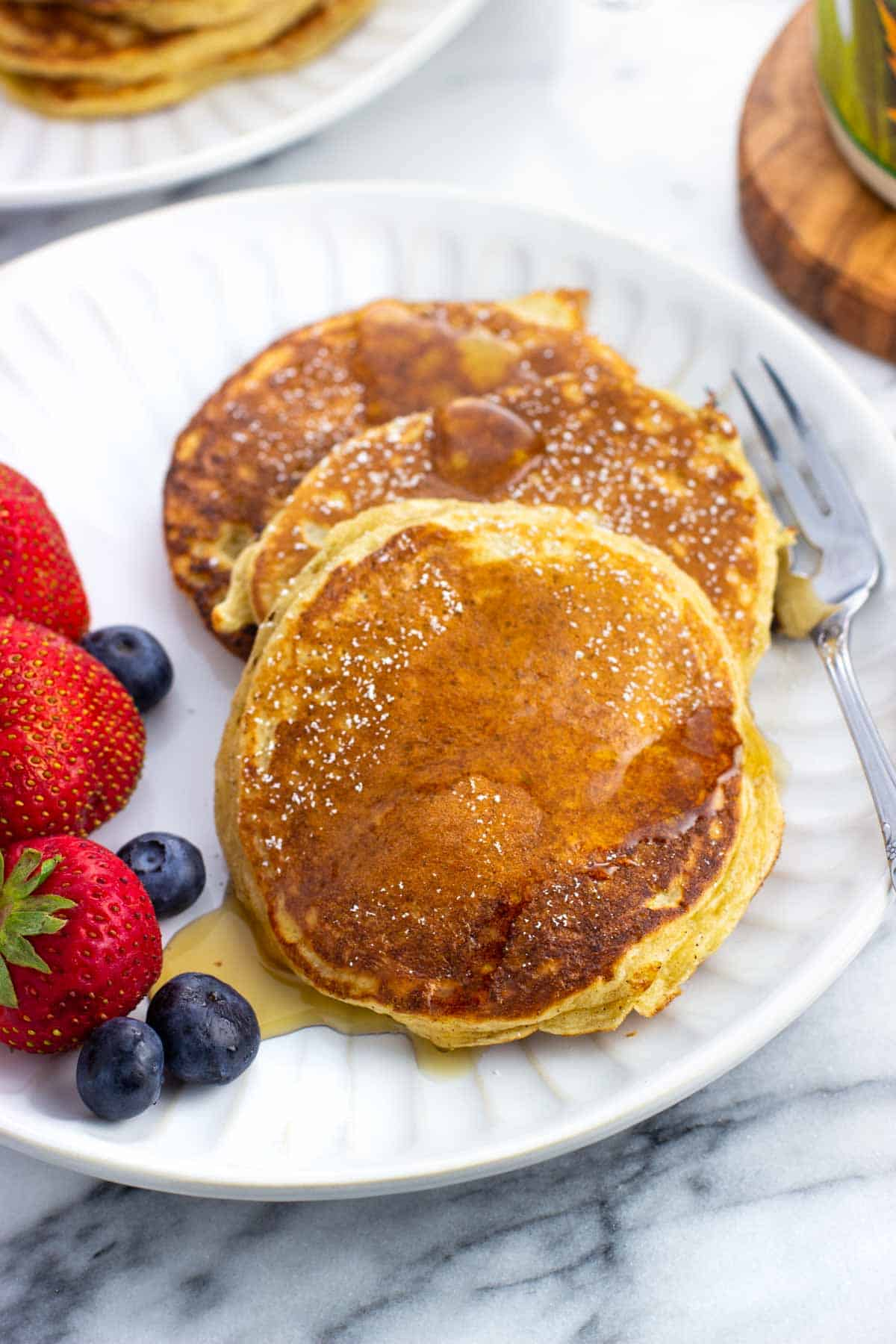 Three cottage cheese pancakes and berries on a plate drizzled with maple syrup.