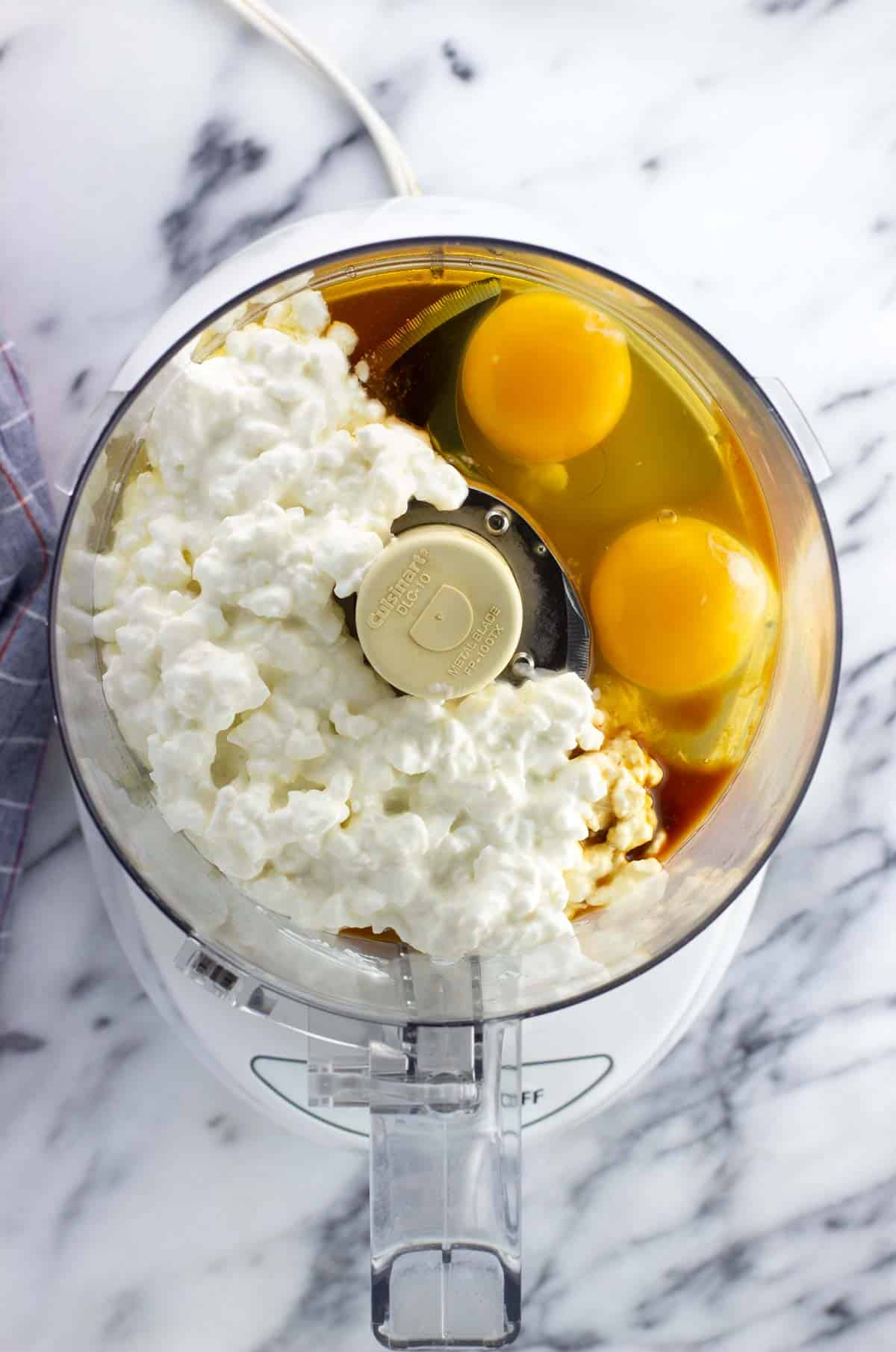 Cottage cheese, eggs, maple syrup, and vanilla extract added to the bowl of a food processor.
