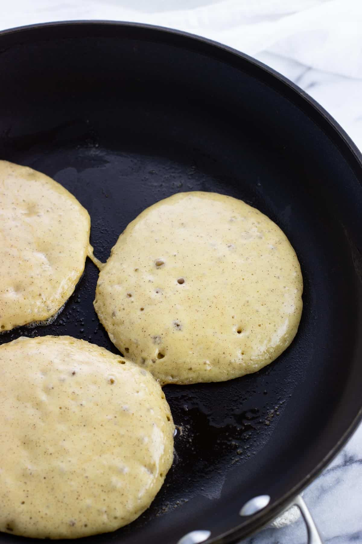 Batter for three pancakes poured onto a hot pan.