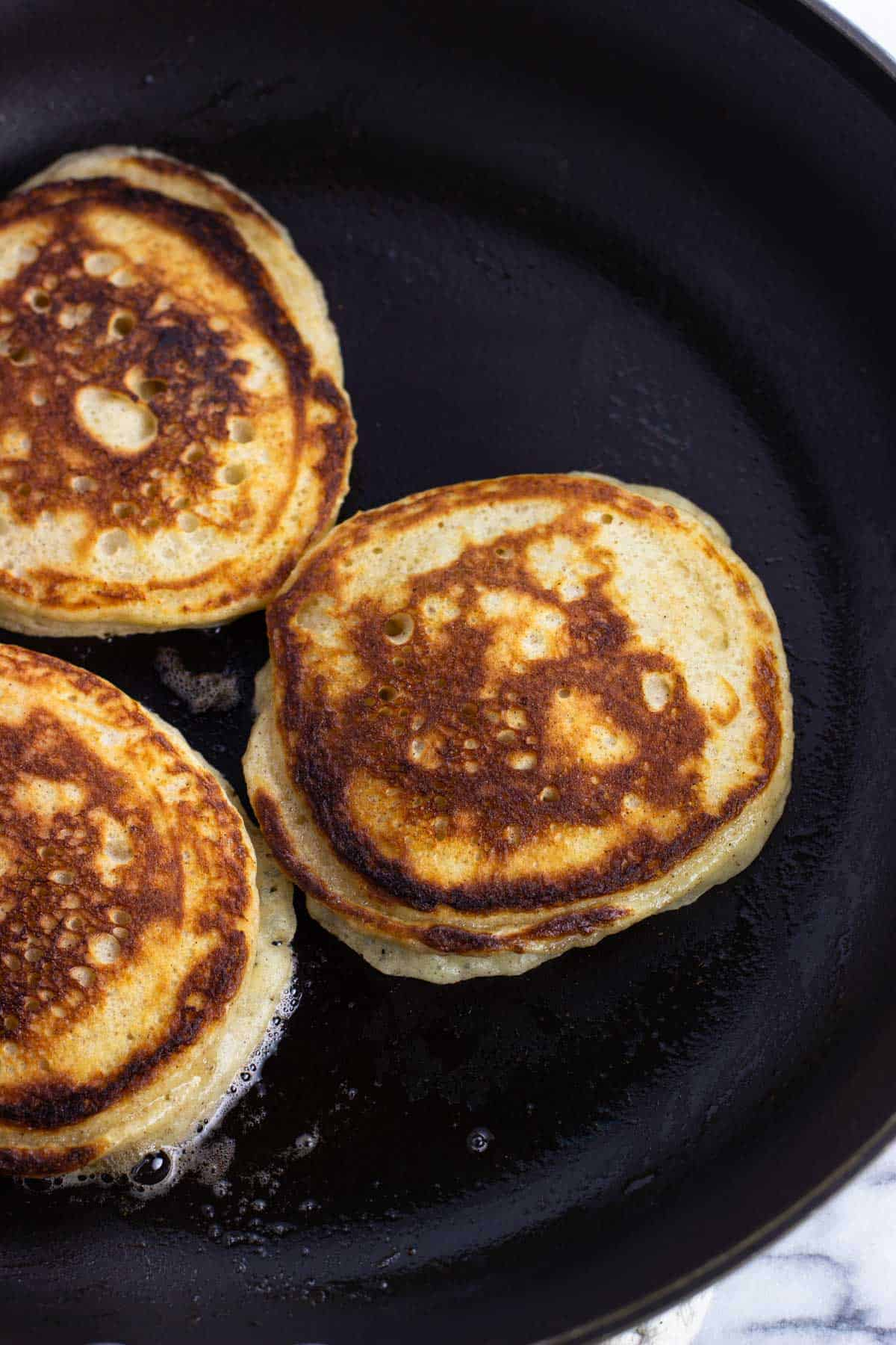Three half-cooked pancakes just flipped on a pan.