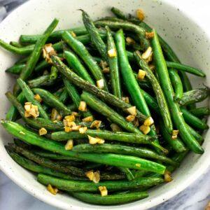 A serving bowl of garlic sauteed green beans.