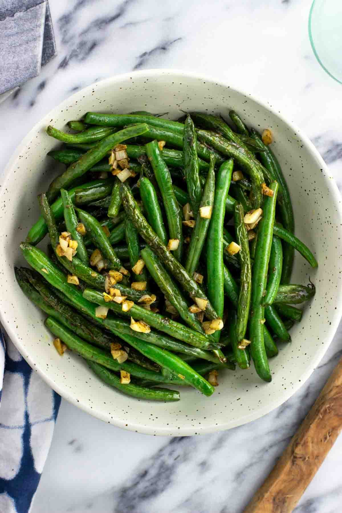 An overhead view of a ceramic bowl of sauteed green beans.