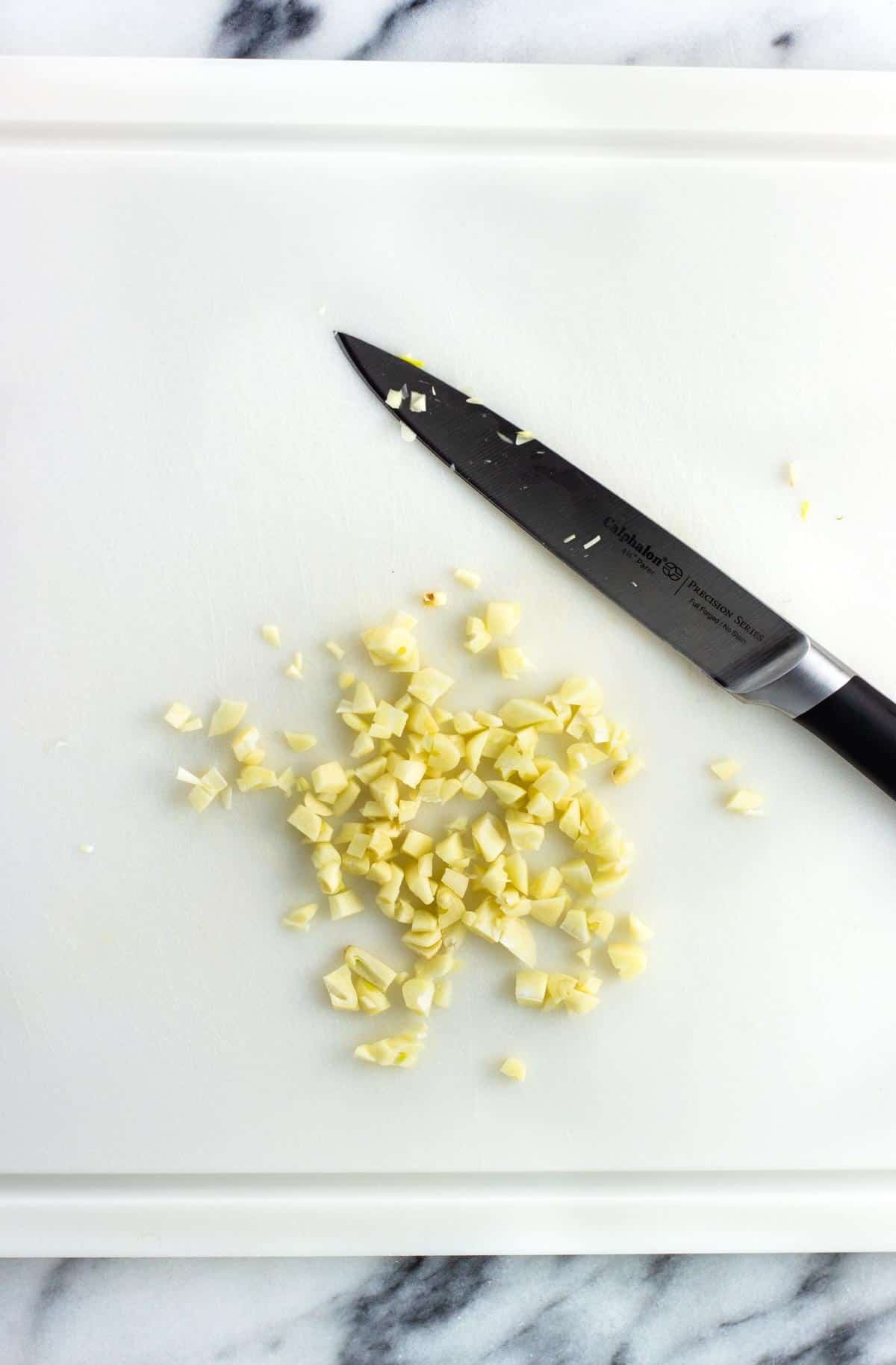Garlic cloves chopped on a cutting board.