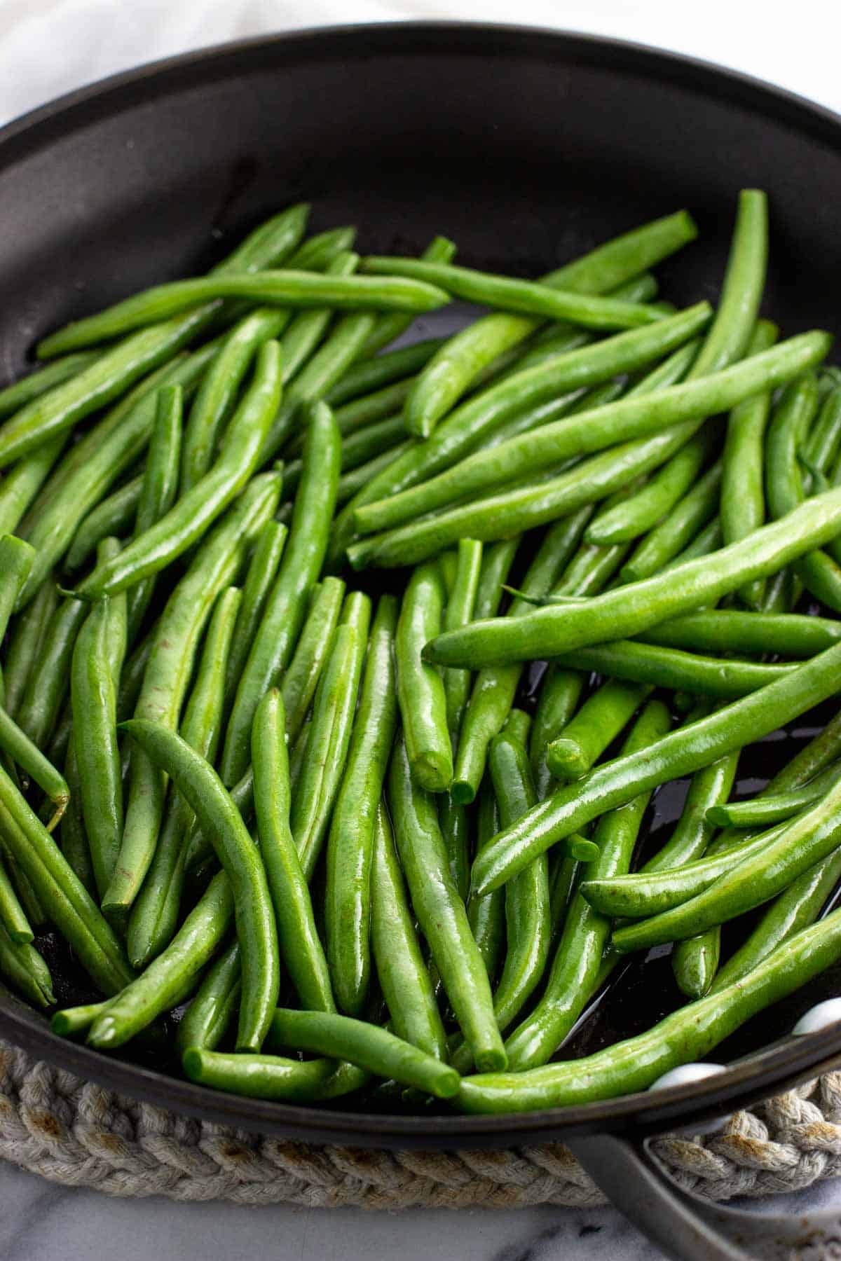 Green beans coated in olive oil in a pan.