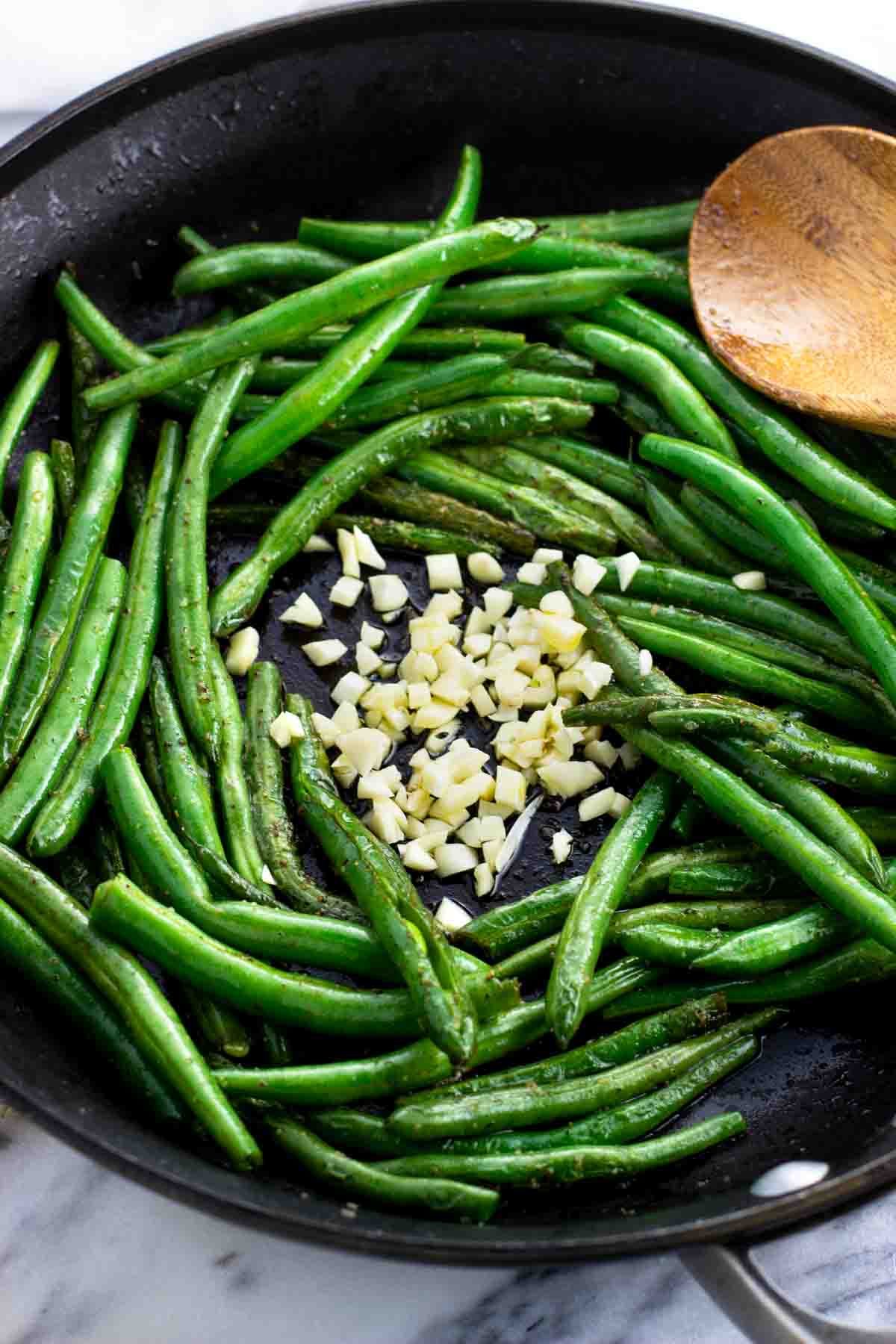 Chopped garlic surrounded by green beans in a pan.