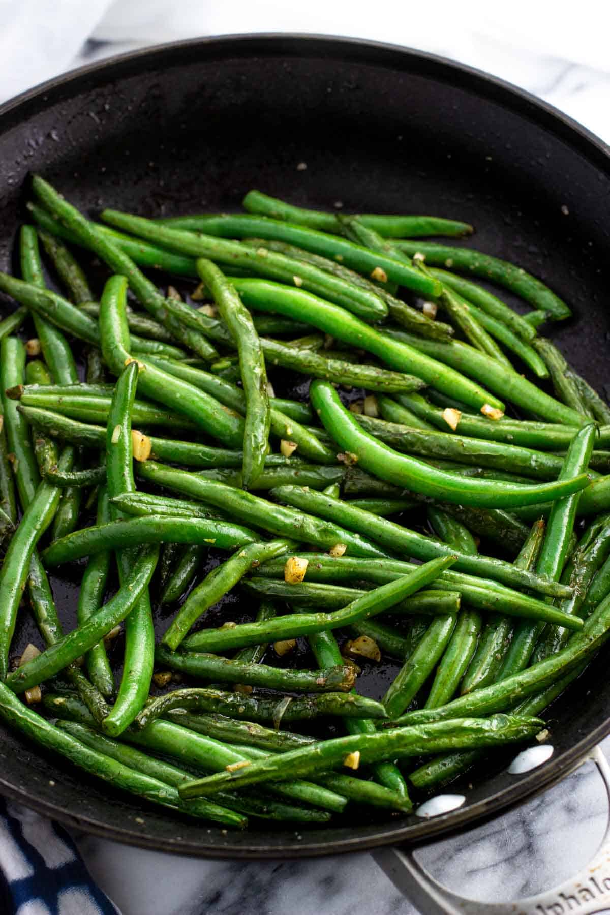 Fully sauteed green beans and garlic in a pan.