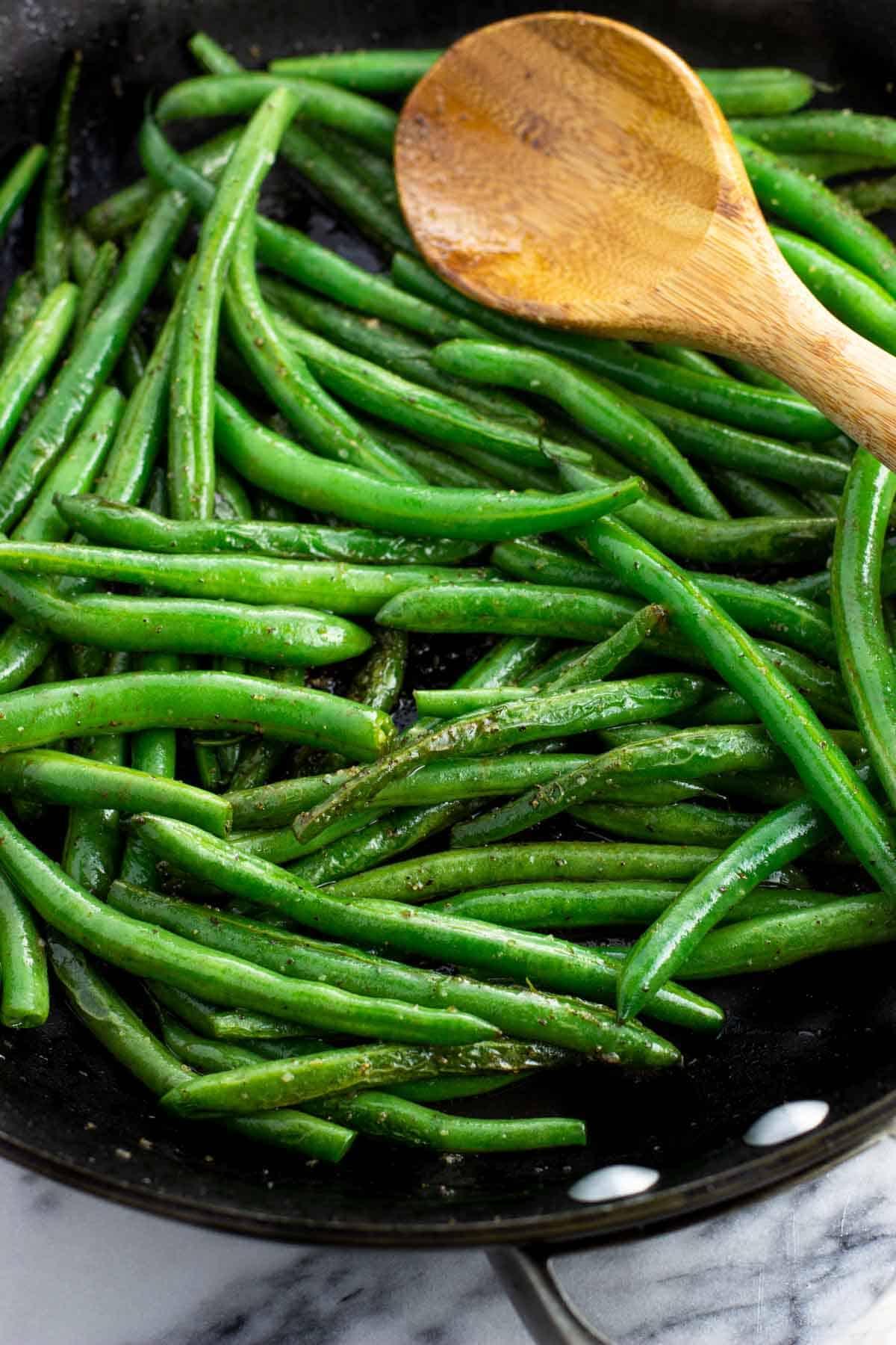 Green beans in a pan with a spoon halfway through sautéing.