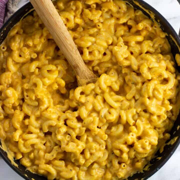 Pumpkin mac and cheese in a pan with a wooden spoon.