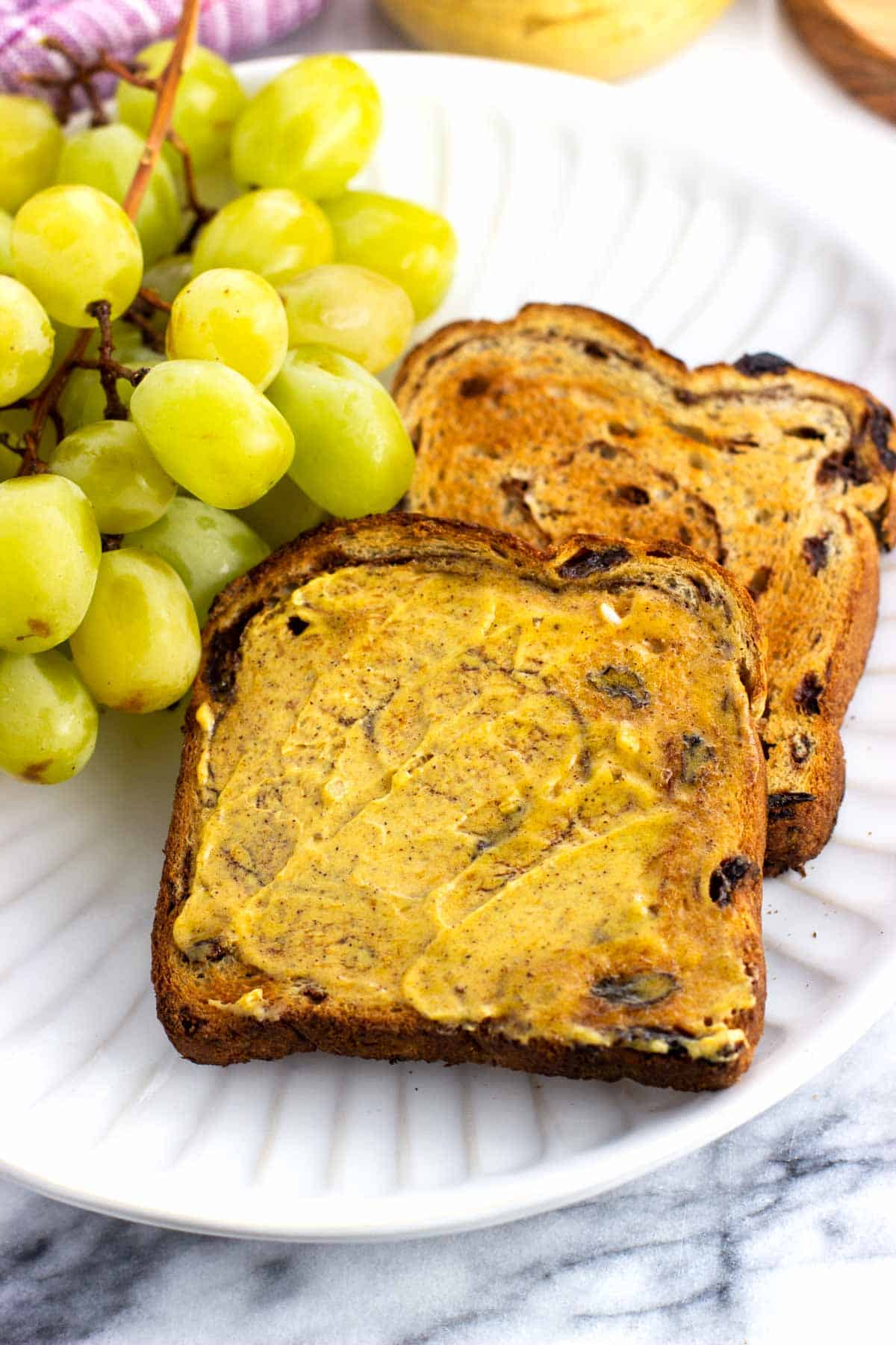 Toast slathered with pumpkin spice butter on a plate with grapes.