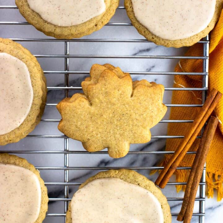Round and maple leaf shaped cookies on a wire rack.