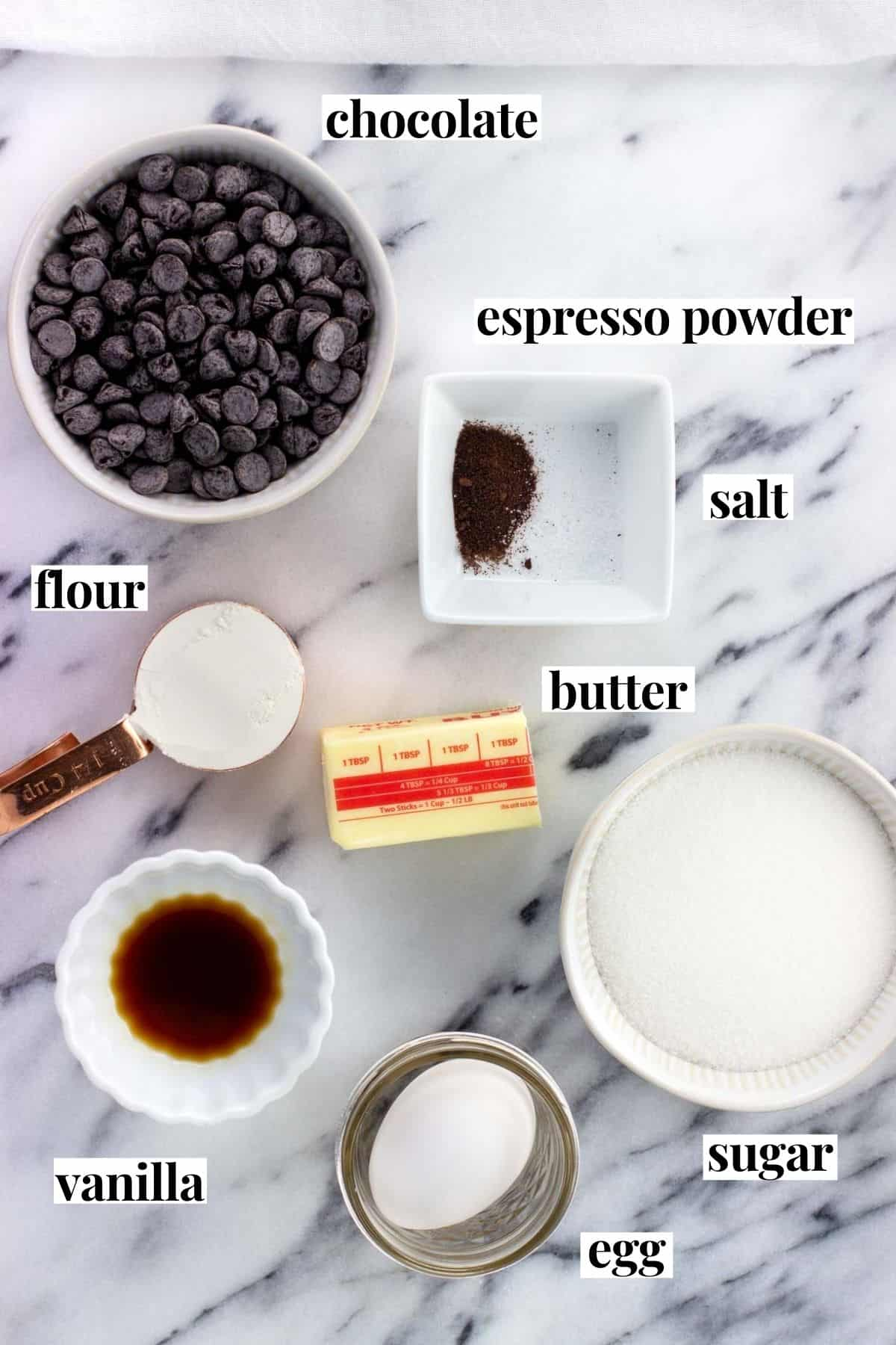 Labeled brownie recipe ingredients on a marble board.
